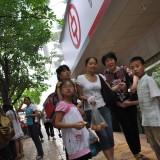 Grupka 5 osób przygląda się z zainteresowaniem osobom rozmawiającym na ulicy przed bankiem w Chinach