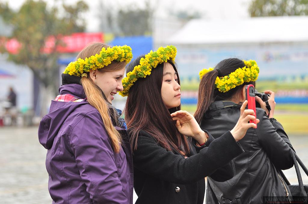 Dziewczyny z wiankami z rzepaku robią sobie zdjęcia.