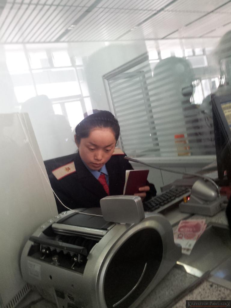 Kasjerka w kasie biletowej na dworcu Fuling Północ wpisująca numer paszportu do systemu przed sprzedaniem biletu
